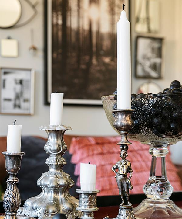 På soffbordet står en samling ljusstakar som hittats på nätauktioner och loppisar