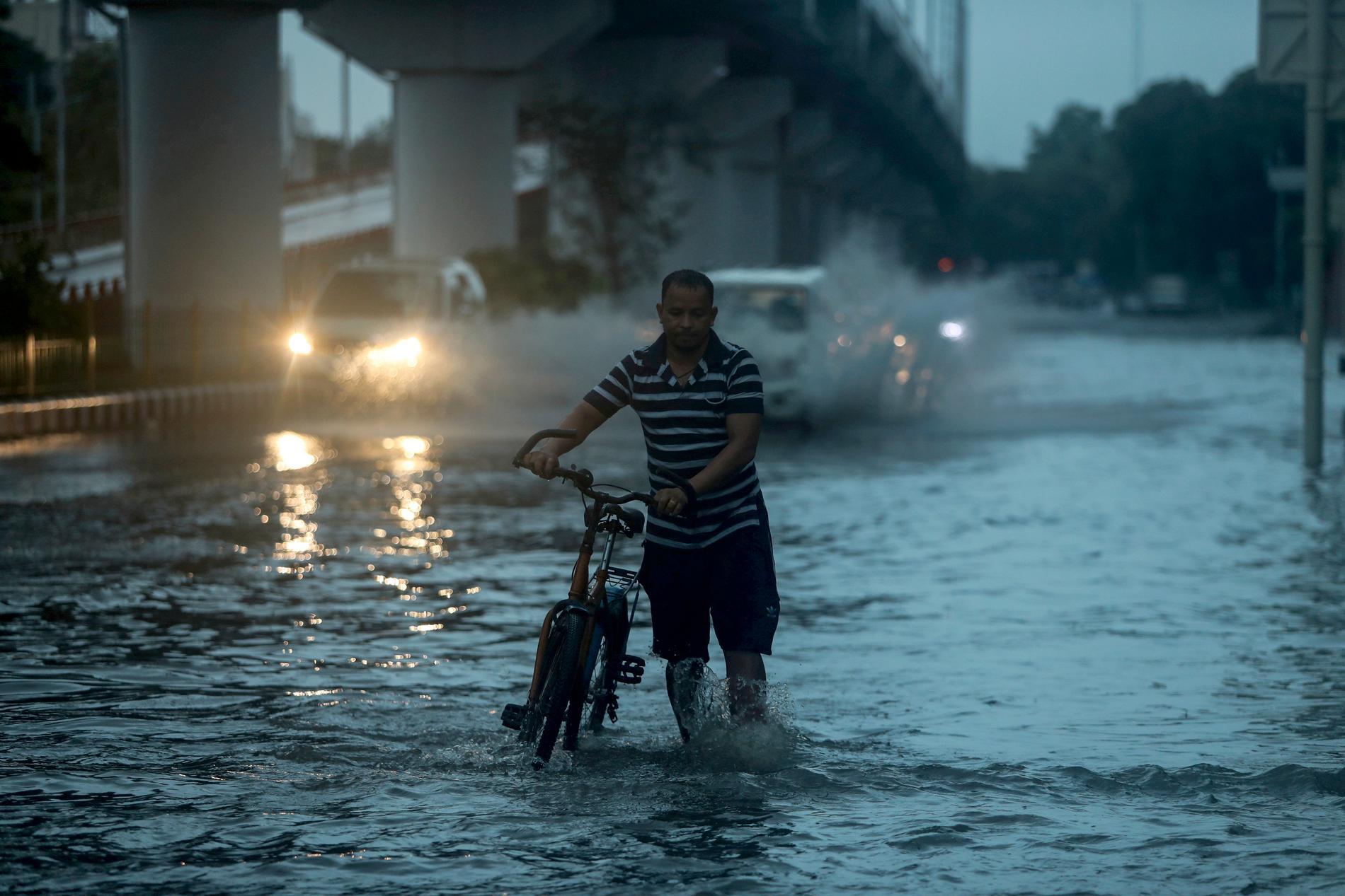 En man vadar med sin cykel genom en översvämmad gata i indiska Jammu.
