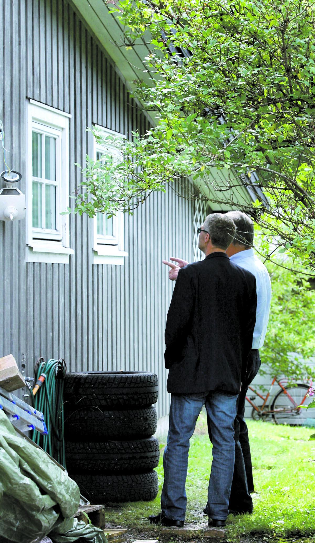 GJORDE EN STEGE AV BILDÄCKEN Thord Haraldsson, chef för Länskriminalen, och kammaråklagare Per Åke Svanström undersöker huset där mannen hittades död. Mördaren har troligen byggt en stege av bildäcken och sedan klättrat in genom ett garagefönster.