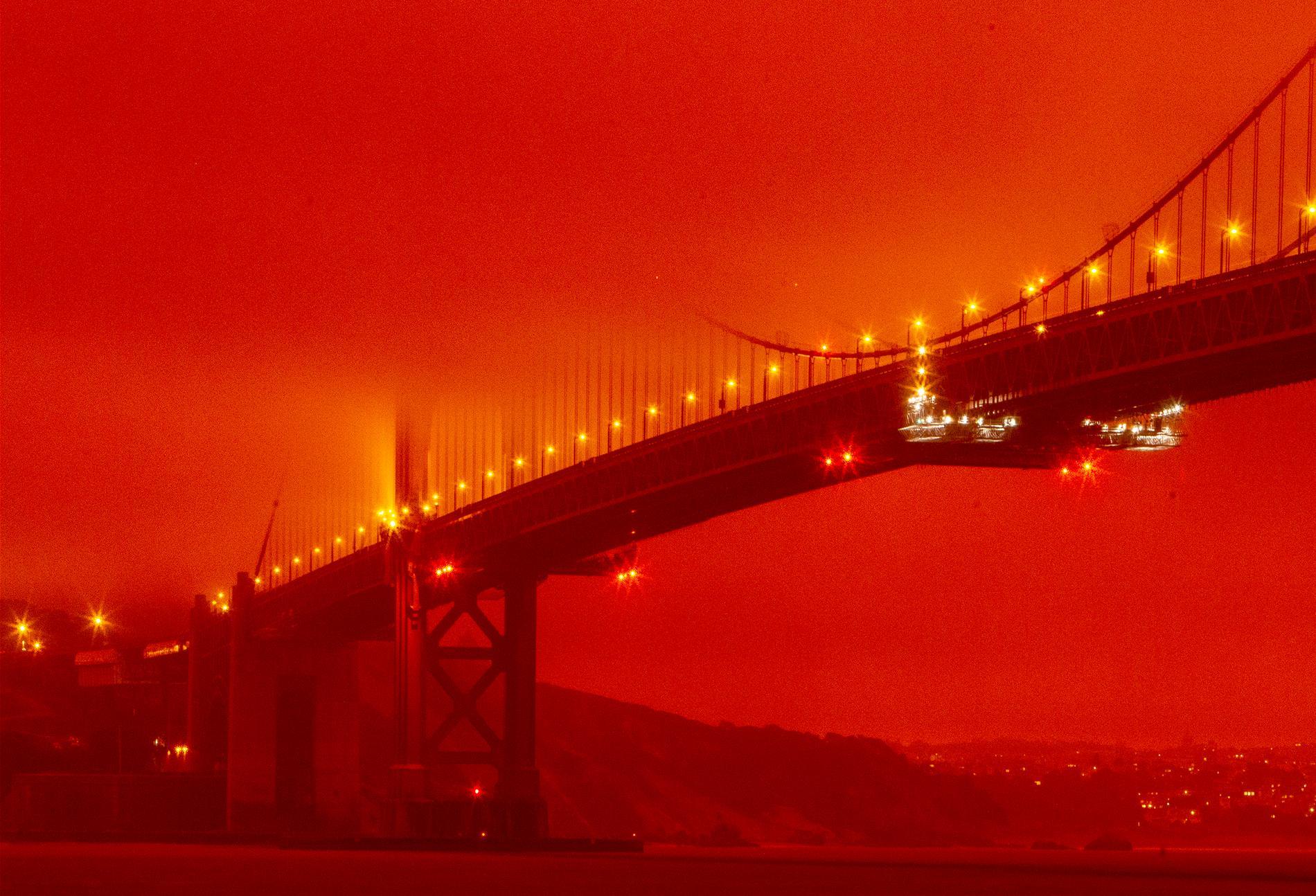 Golden gate-bron täcks av skenet från de pågående skogsbränderna i omgivningen.