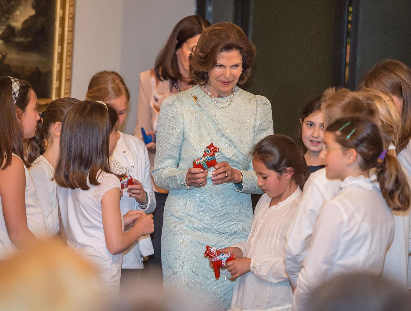 Silvia delar ut Dalahästar till barnen.