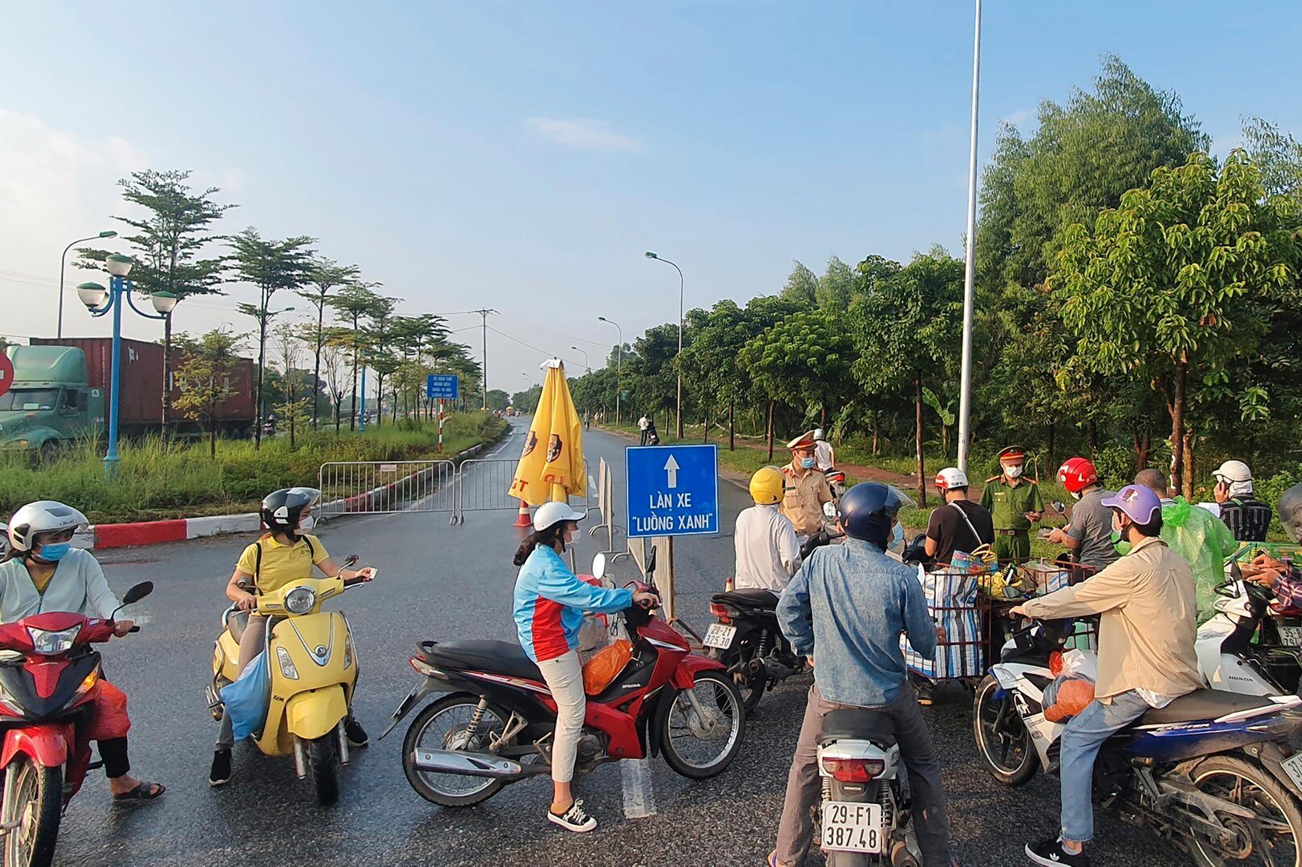 En vägspärr hindrar människor från att ta sig in i Hanoi, som stängde ner på lördagen för att stoppa virusspridningen.