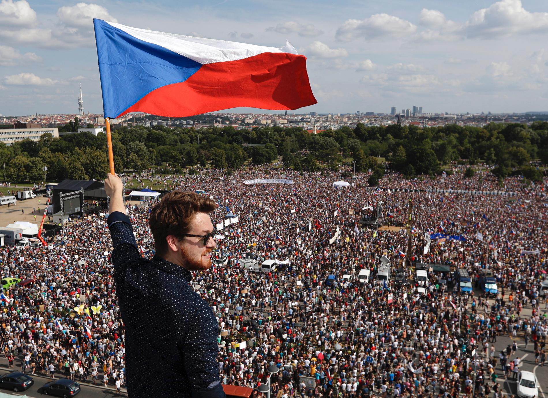 En man håller i den tjeckiska flaggan. I bakgrunden syns de tusentals demonstranter som samlats i Tjeckiens huvudstad Prag för att kräva premiärministerns avgång.