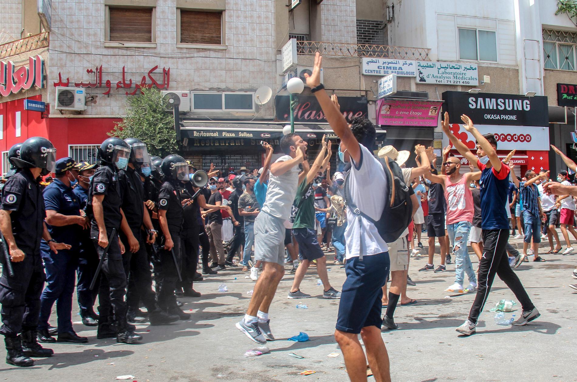 Demonstranter drabbar samman med polis i Tunisiens huvudstad Tunis under söndagen. Våldsamma demonstrationer har brutit ut på flera håll i landet i protest mot landets styre.