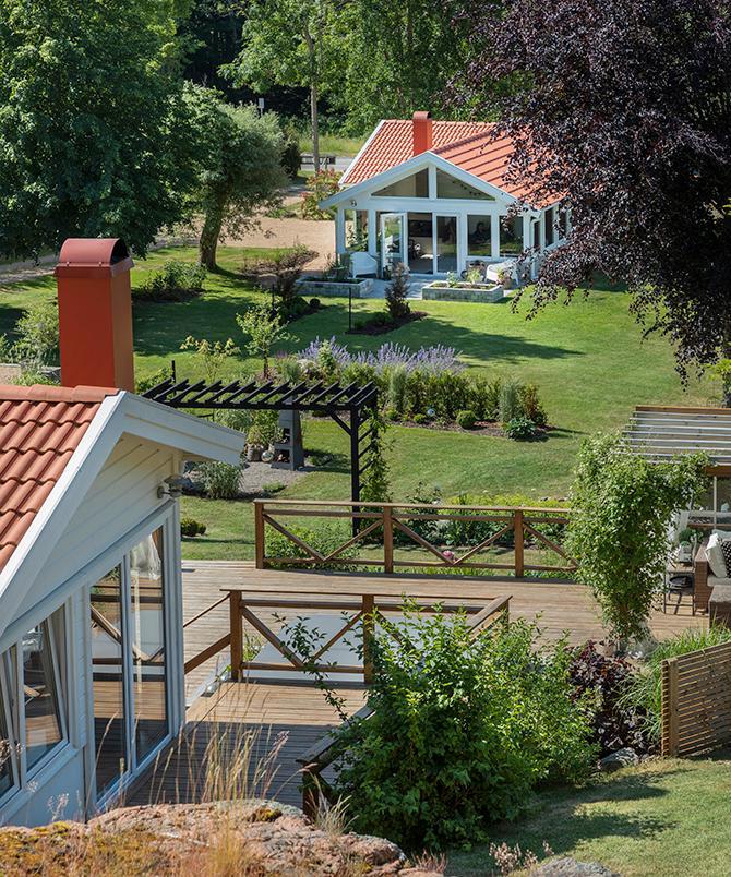 Uppifrån berget har man utblick över hela trädgården med altandäck i olika etage, rosenbågen, perennrabatterna, uteplatserna och orangeriet.