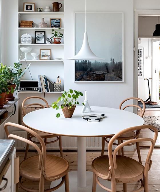 Det runda bordet kommer från Ikea och runtom står klassiska Thonet-stolar i obehandlad bok. Josefine älskar gröna växter och tack vare ljusinsläppet från de 24 fönsterna så stortrivs de. De inbygga hyllorna är original och rymmer porslin och vackra reseminnen.