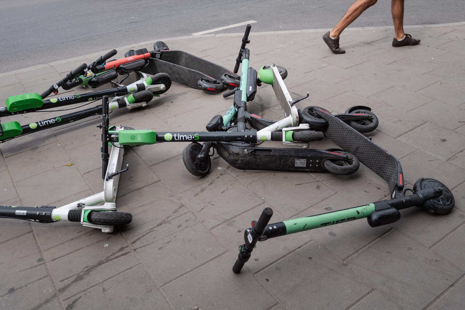 Elsparkcyklar lämnade liggande på en trottoar.