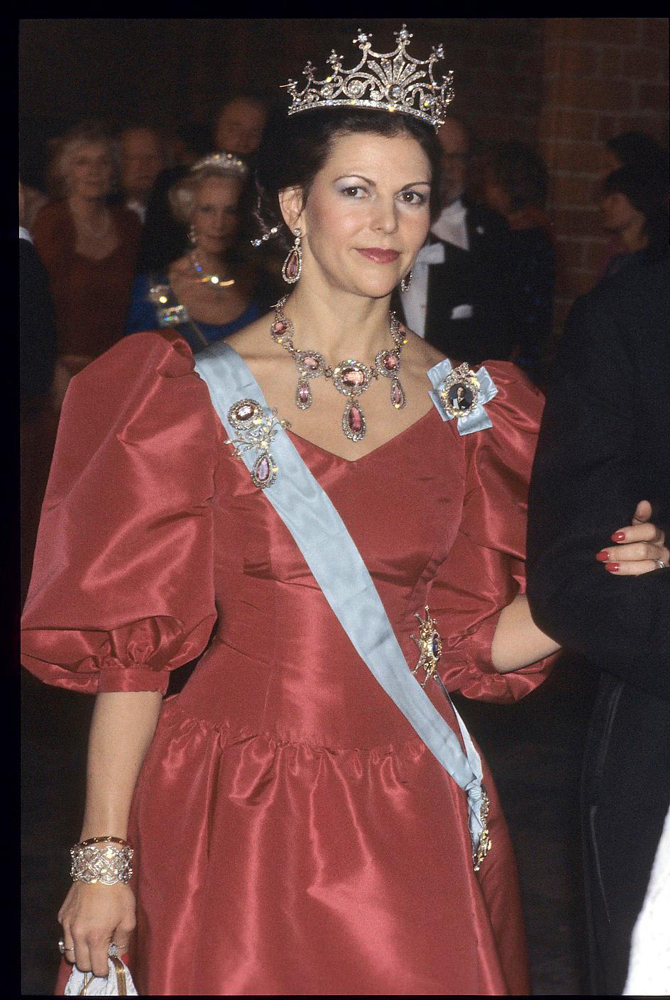 1983.Andra året i rad för den danske hovskräddaren Jørgen Bender att få det ärofyllda uppdraget. Frågan är om han inte inspirerats av drottning Diana Spencers berömda bröllopsklänning, med de enorma puffärmarna, som sågs två år tidigare. Ädeltopasgarnityret och drottning Sofias diadem i håret.