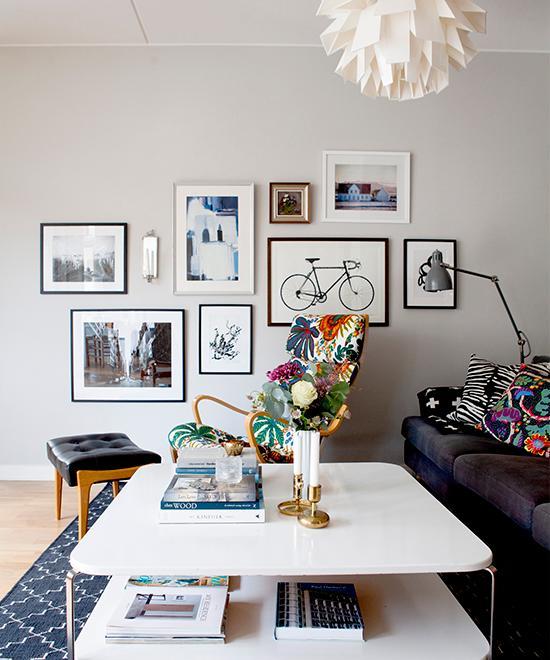 """Snygga detaljer i vardagsrummet. Soffbordet är köpt på loppis för 50 kronor. Fåtöljen med Josef Frank-klädsel köpt på Stockholms auktionsverk och tavla med """"Världsmästarcykeln"""" från Grandpa."""