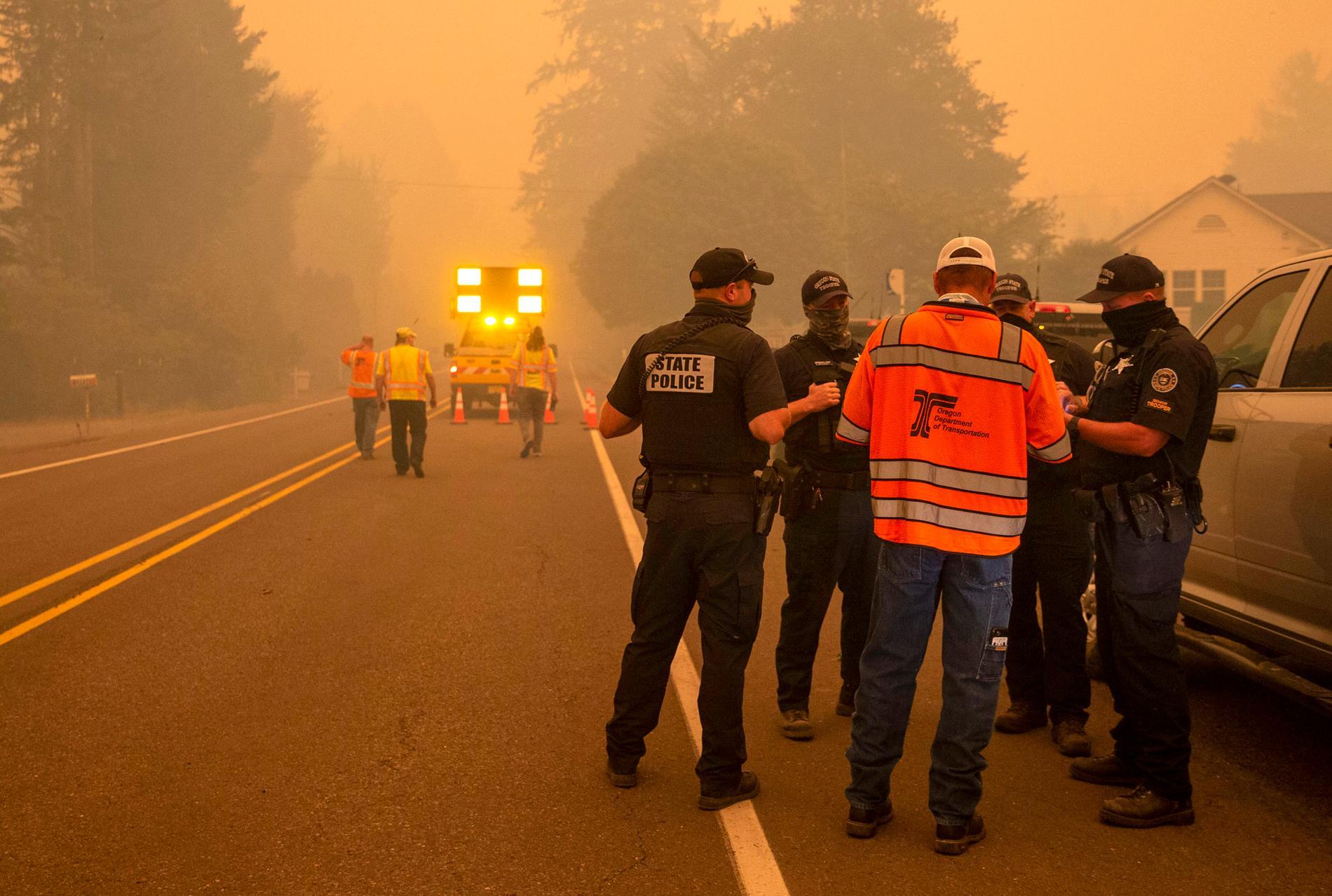 Poliser på plats vid en vägspärr. En halv miljon människor har fått order om evakuering i samband med bränderna.
