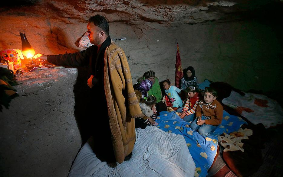 skydd från bomber Adnan al-Hamod tänder en lampa i familjens skyddsrum – en underjordisk grotta. I krigets Syrien blir romerska gravar och andra fornlämningar till nya hem för civila.