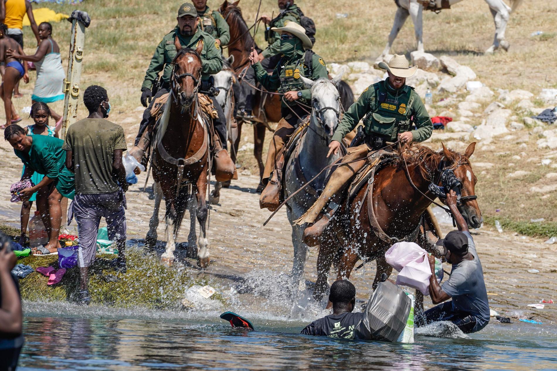 Migranter prejas ner av gränspoliser på häst.