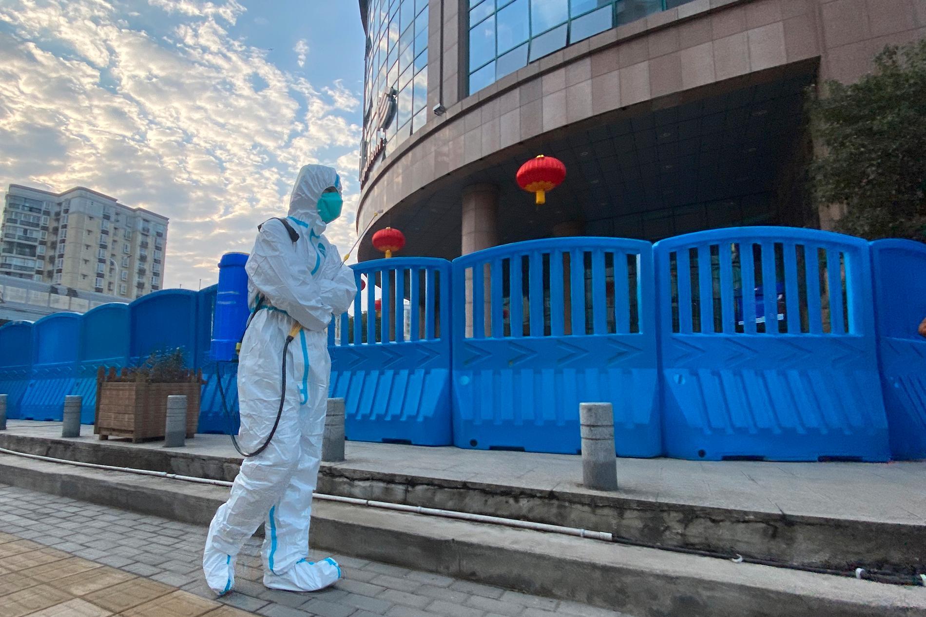 En person i skyddskläder utanför ett sjukhus i Wuhan i Kina. Nu gör WHO ett nytt försök att hitta coronavirusets ursprung. Arkivbild.