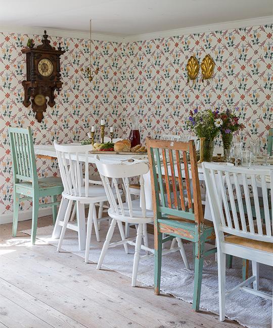 I det stora rummet, som fungerar som vardagsrum och matsal, står ett bord som Sten byggt själv av vitmålade golvplankor och bockben från Ikea. Runtom står tolv blandade loppisstolar. Väggklockan är arvegods.