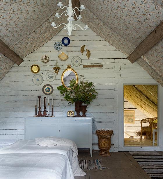 Råvinden har förvandlats till ett stort enormt luftigt sovrum. För att få till en ombonad känsla har taket klätts med ett tyg med allmogemönster, handtryckt på Rydboholms textil.