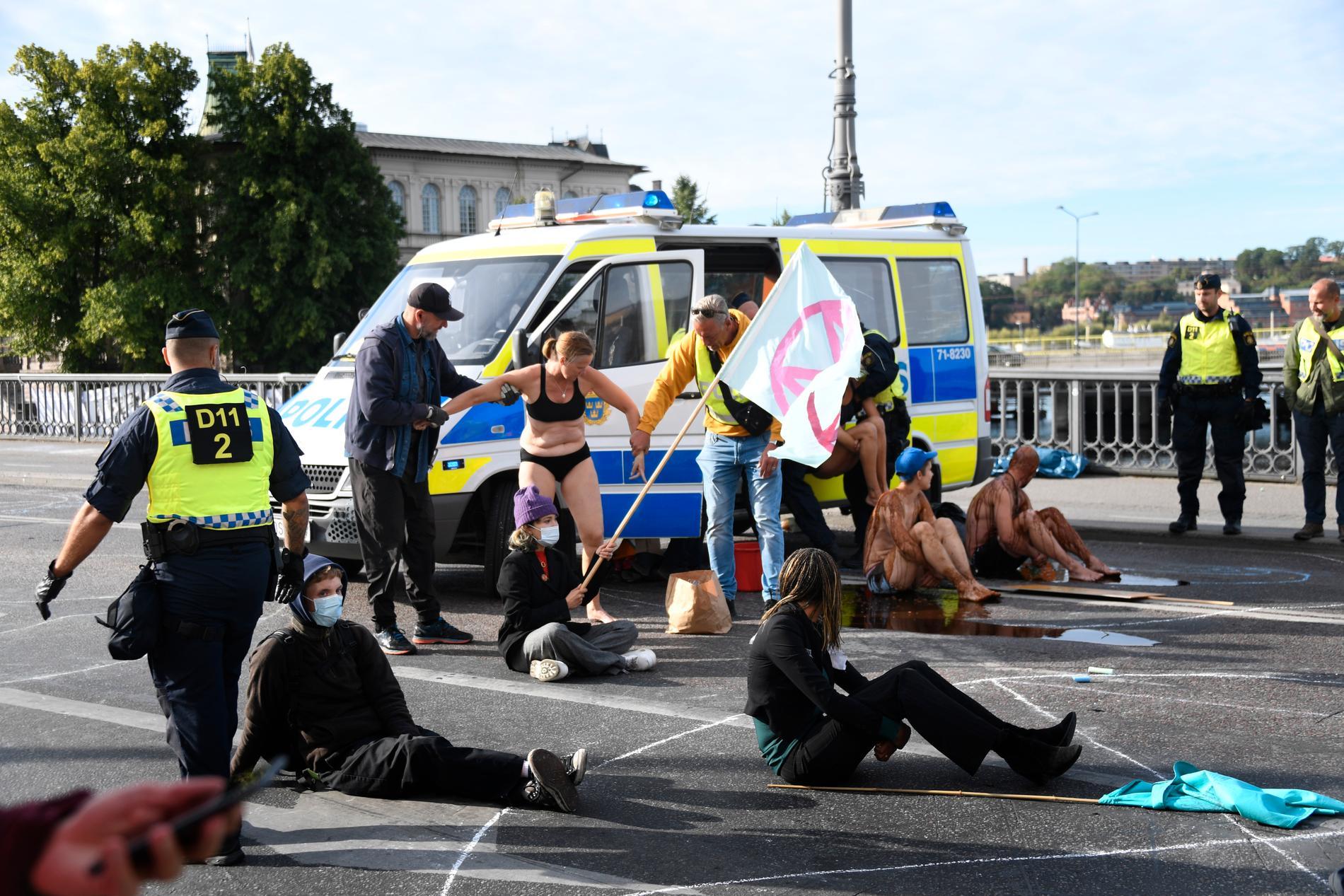 Polisen avlägsnar en demonstrant på Vasabron i Stockholm.