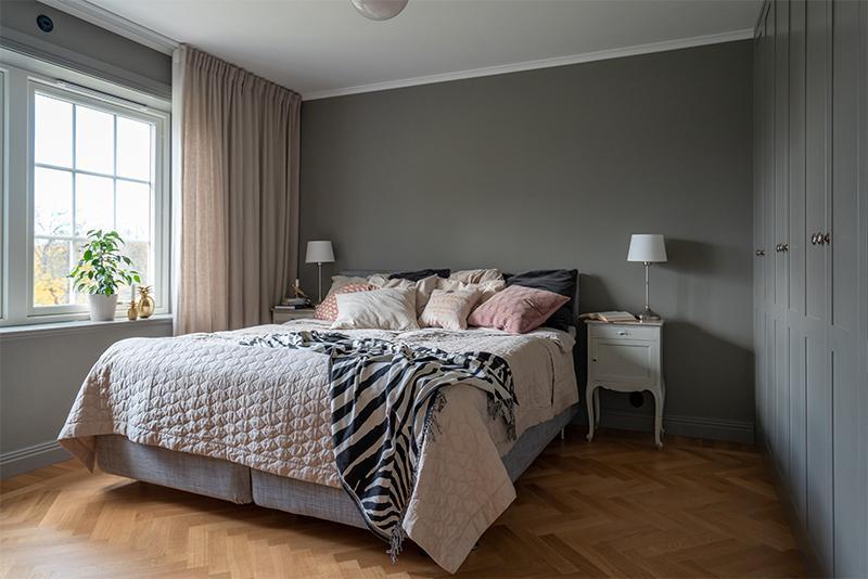 I sovrummet är både väggar, lister och garderobsdörrar målade i en mörkgrå kulör för ett sammanhållande och stillsamt intryck. Färgkod, S4502-Y. Sängbord, arvegods efter Emilias farmor. Sänglampor, Ikea, garderobsdörrar, Järfälla kök, pläd, H&M home.