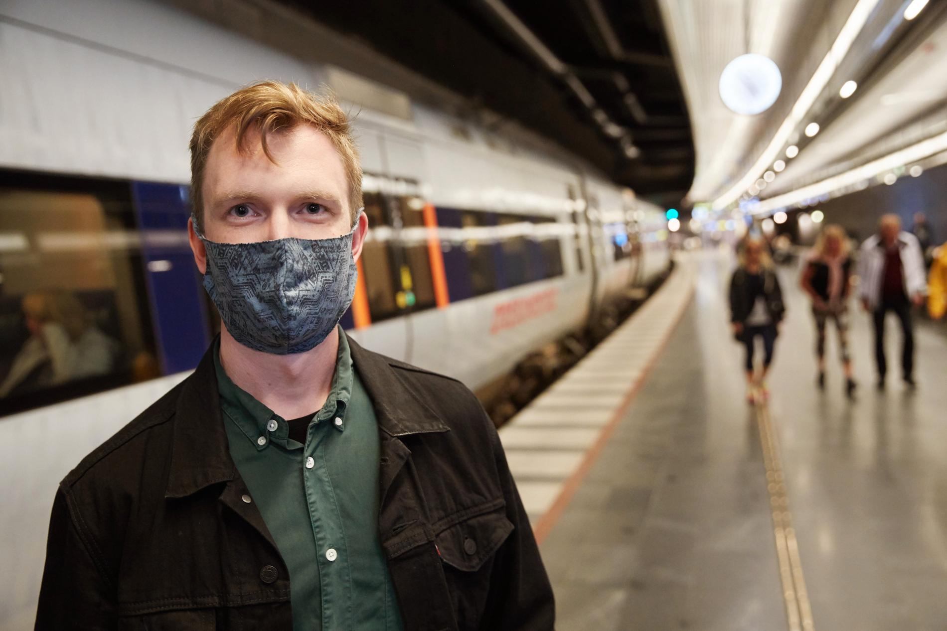Carl Flyman bär munskydd på tåget.