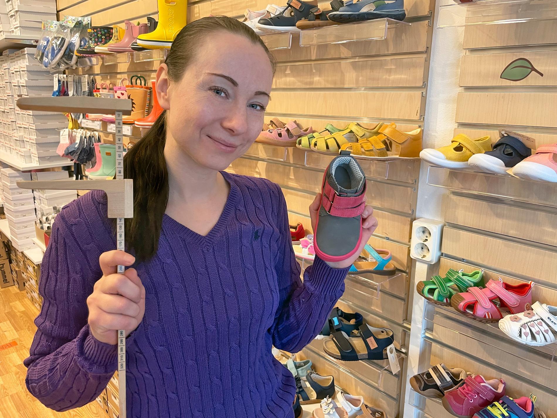 Tatjana visar upp en sko och mätsticka i sin butik Promenix. Hon ger råd på hur du väljer rätt storlek på skor till ditt barn.