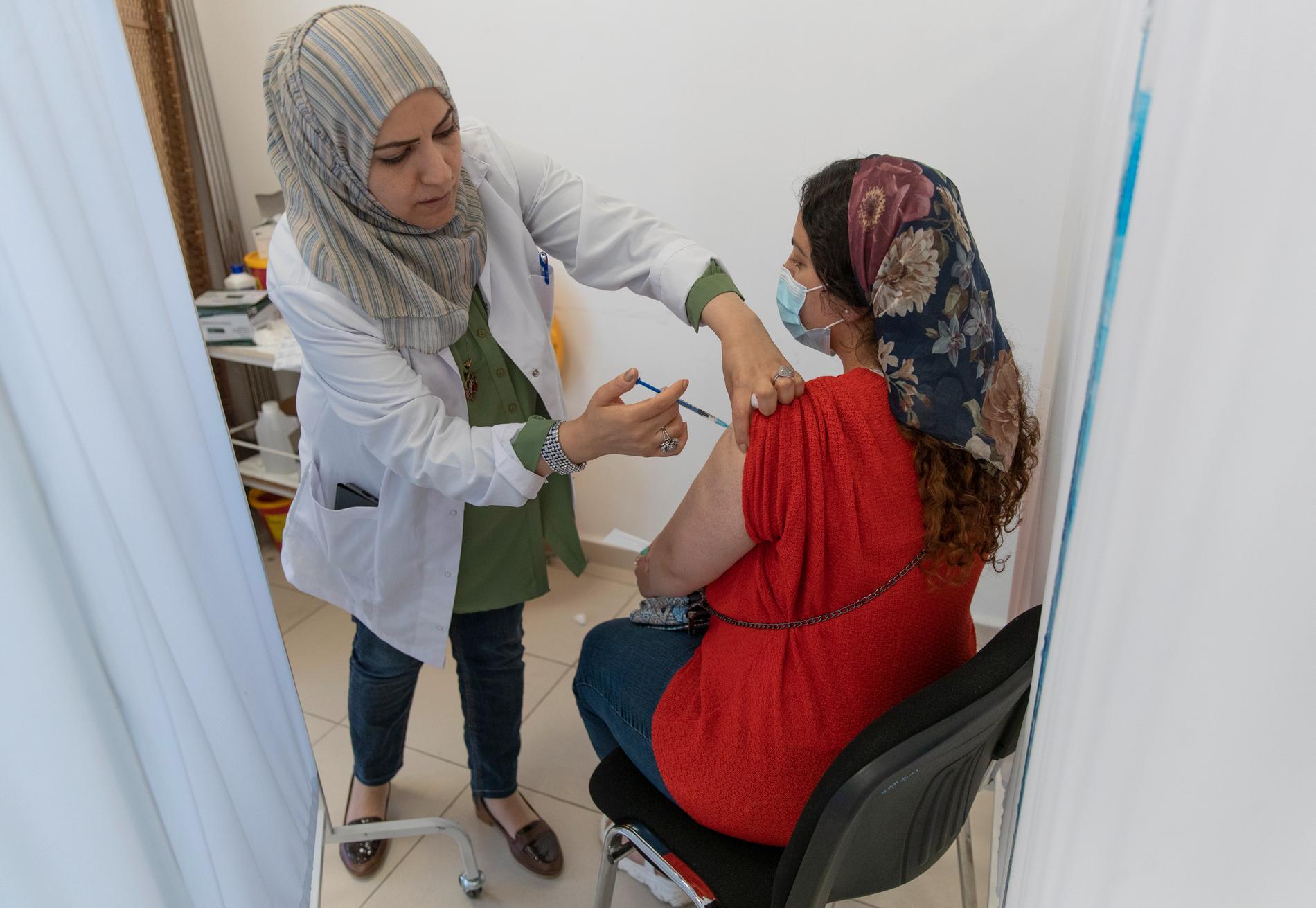 Sköterska i Ramallah på Västbanken vaccinerar en kvinna i början av juni.