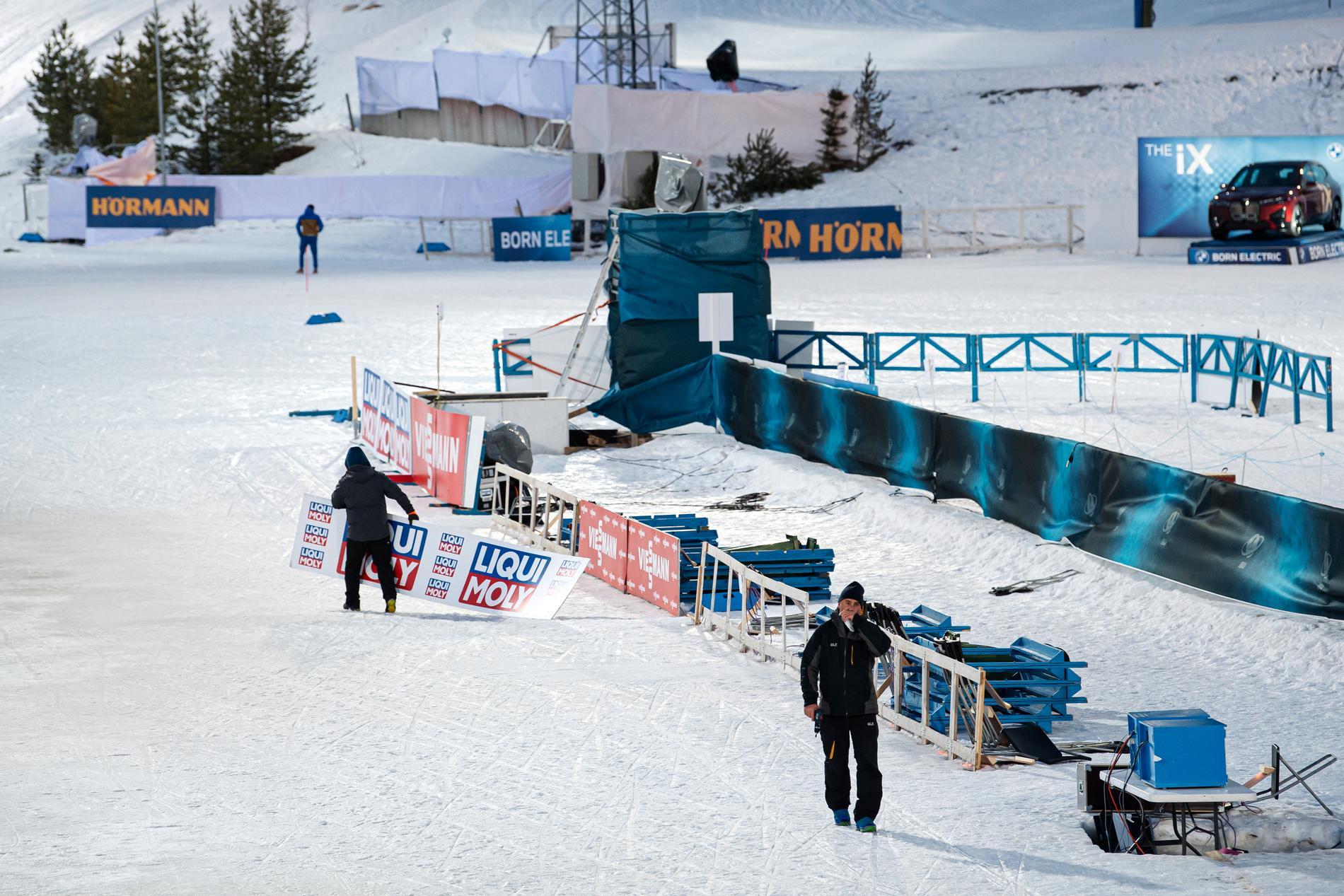 Funktionärer fick kämpa med att hämta flygande reklamskyltar på skidskyttebanan.