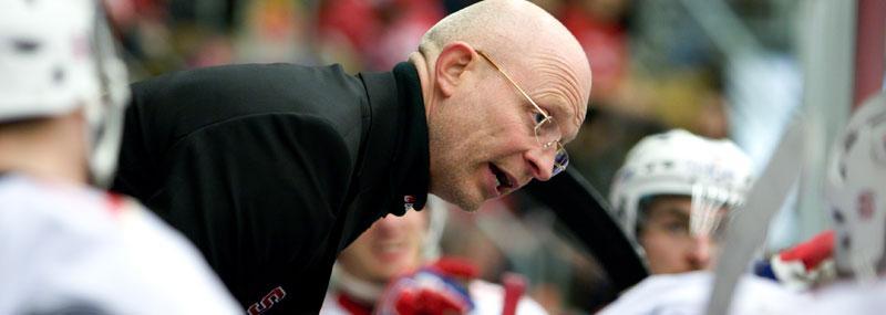 Södertäljes tränare Jim Brithén skyddas av vakter efter trakasserier.