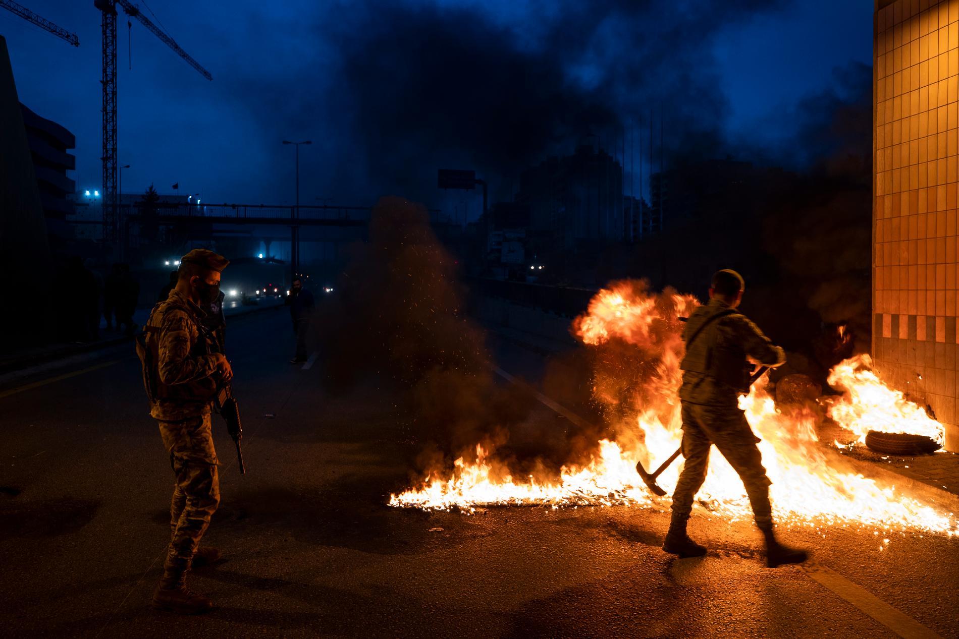Libanesisk militär städar undan brinnande däck.