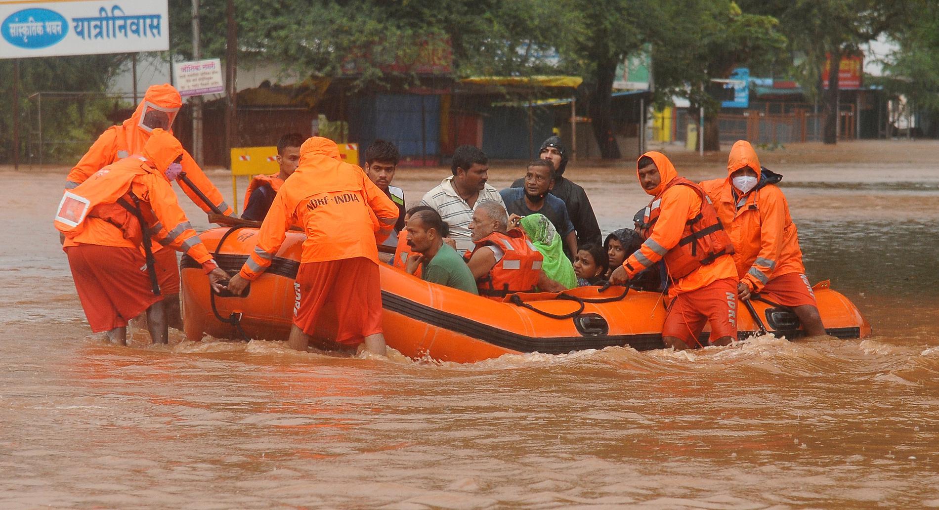Räddningspersonal evakuerar människor som strandsatts i översvämningar i Kolhapur i västra Indien, efter kraftiga monsunregn.