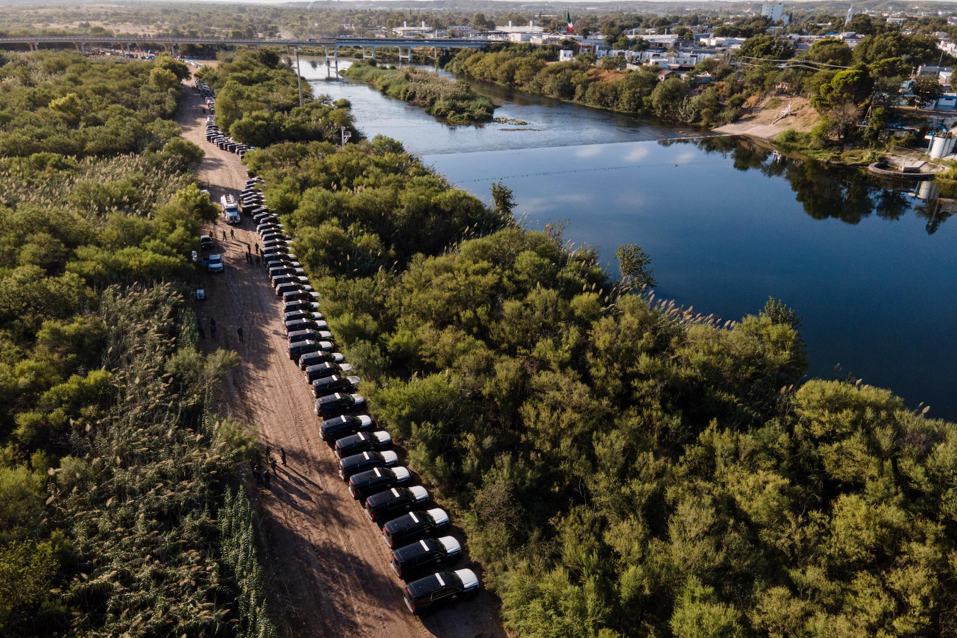 En rad av fordon vid Rio Grandes flodbank. Tanken är att de ska hindra folk från att korsa gränsen.