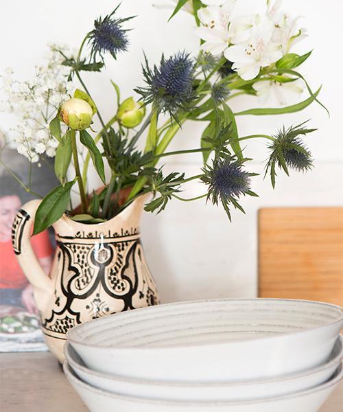 För att mjuka upp köksinredningens strikta karaktär har Joy valt att exponera keramik, terakotta, trä och växter på bänkskivorna.