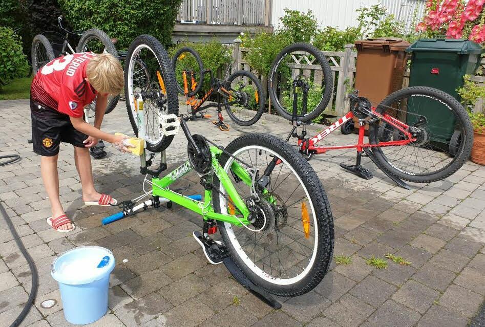 Här tvättar Oliver kundernas cyklar på familjens uppfart.
