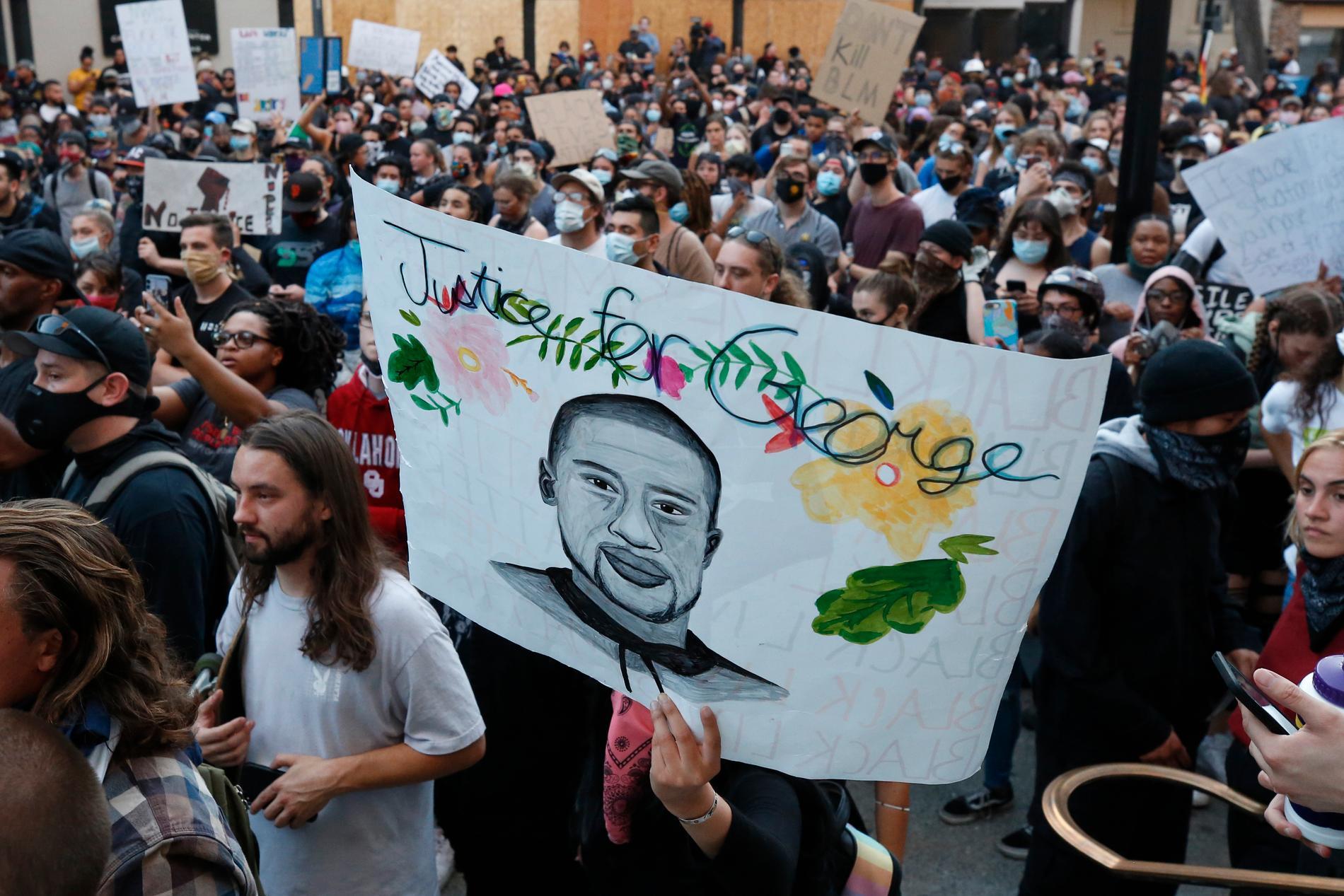 Demonstranter håller upp ett porträtt av George Floyd under en av många protester mot polisvåldet i USA.