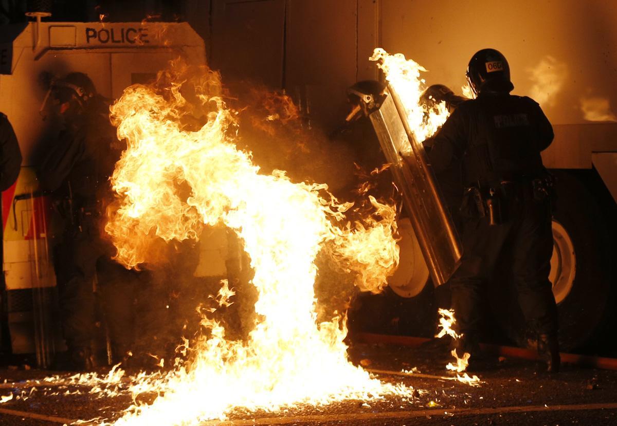 Nordirländska poliser försöker släcka en brandbomb kastad av protestantiska lojalister under upplopp i Belfast 2013.