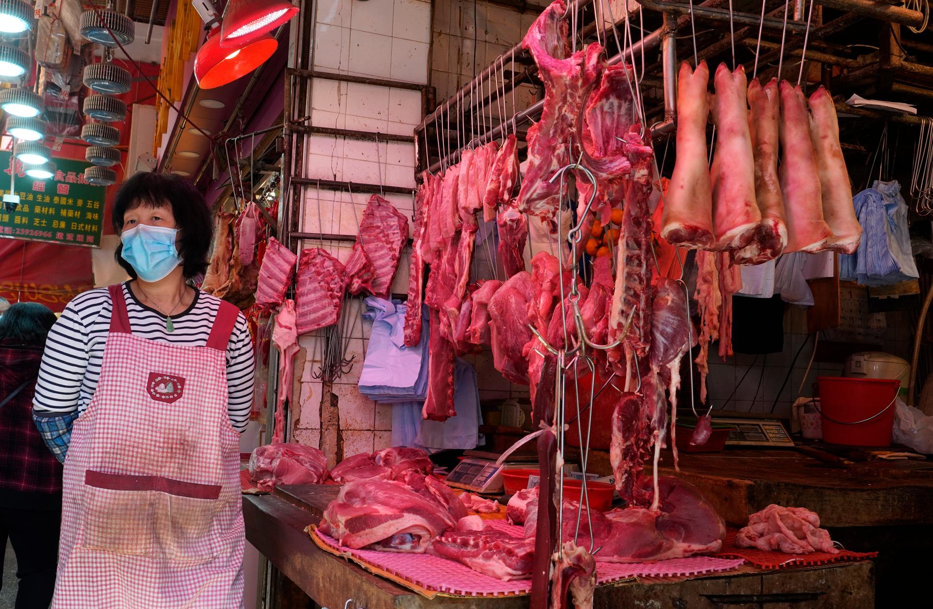 En anställd klädd i ansiktsmask på en köttmarknad i Hong Kong i januari.