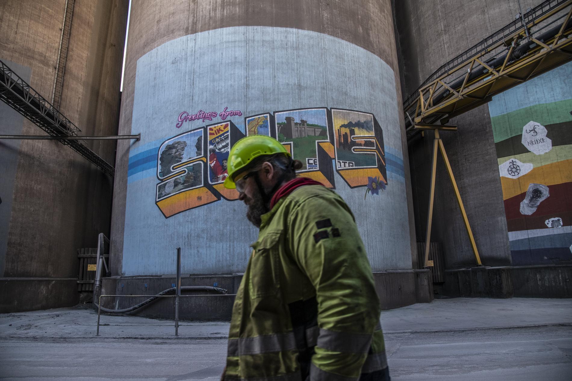 En arbetare passerar muralmålning i Cementas industriområde