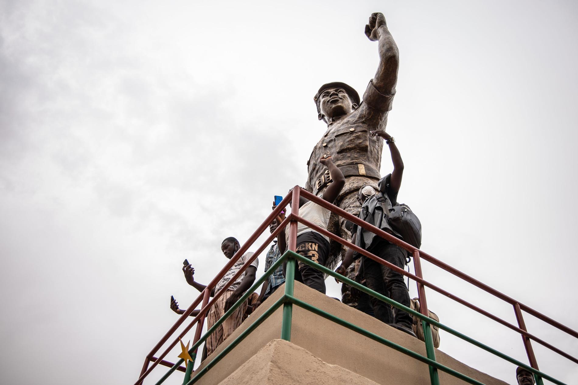 Anhängare poserar vid den omarbetade statyn av Burkina Fasos före detta president Thomas Sankara då den presenterades den 17 maj i huvudstaden Ouagadougou.
