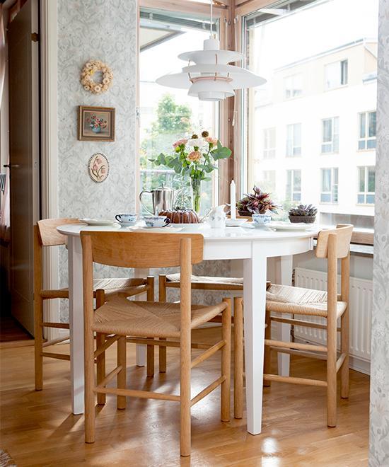 Flödande ljus i köket. Köksbord köpt på Blocket, stolar J39 av Børge Mogensen och lampa PH 5 av Poul Henningsen. Tapeten heter Thistle från Boråstapeter. På väggen syns en krans av eterneller som Hanna gjort.