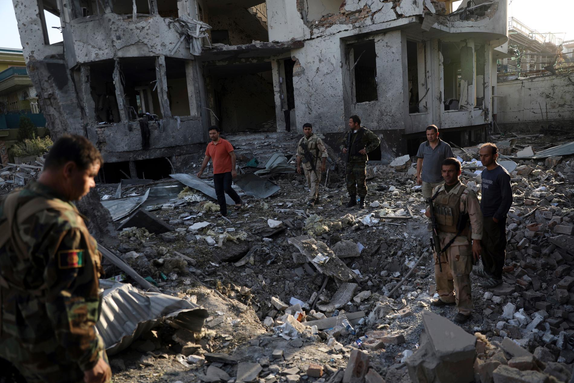 Säkerhetspersonal inspekterar en byggnad som skadats i en attack nära Kabuls diplomatkvarter.