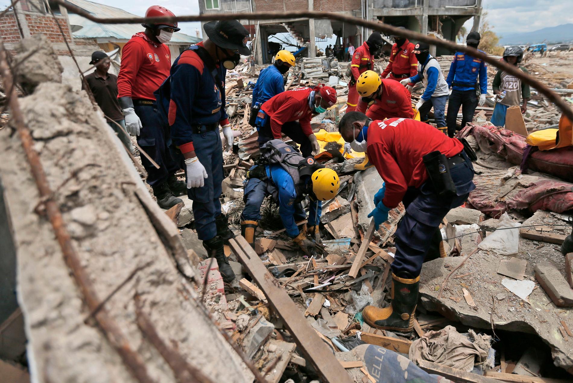 Räddningsarbetare letar efter offer i ruinerna i staden Palu.