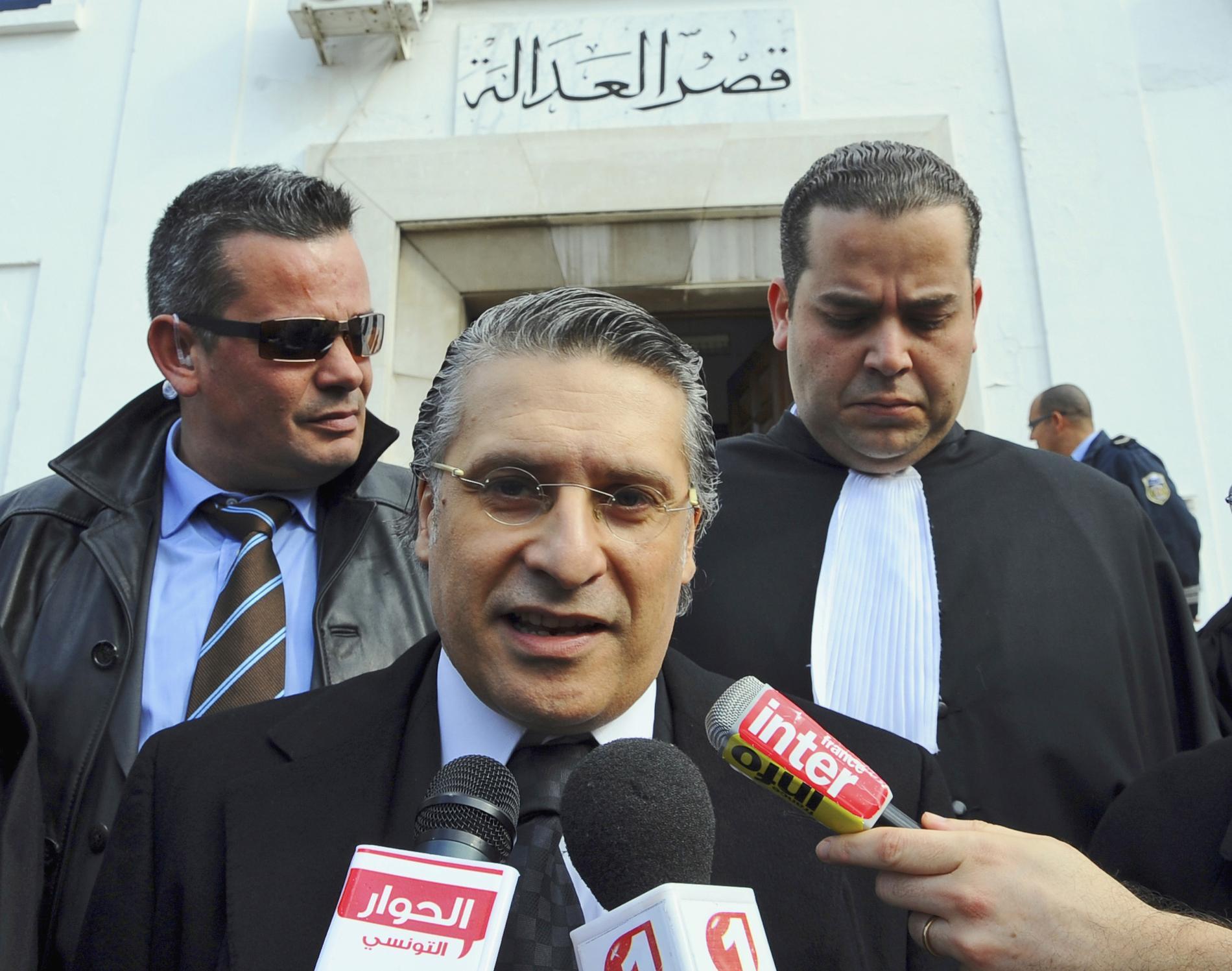 Presidentkandidaten Nabil Karoui (mitten). Arkivbild.