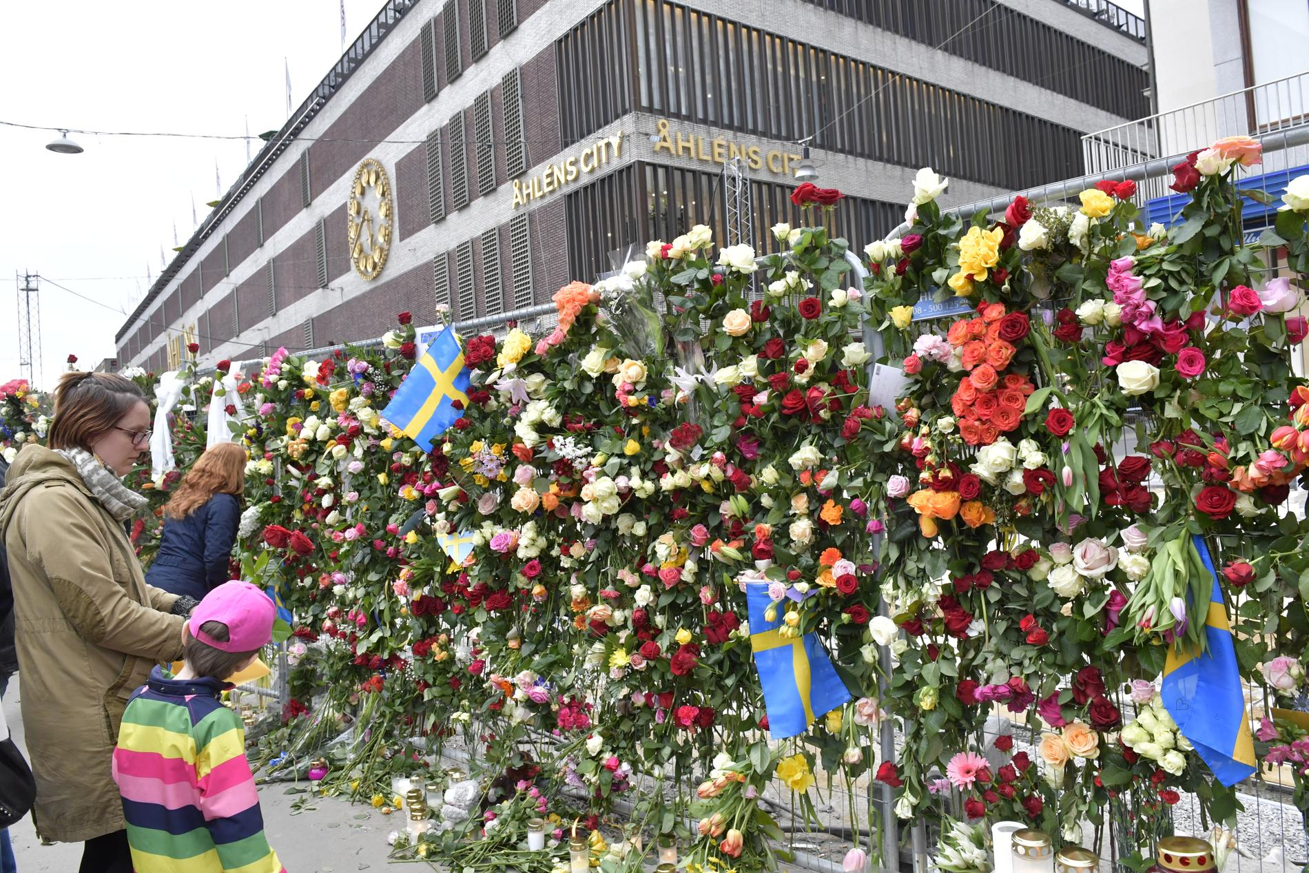 Människor besöker avspärrningarna vid Åhléns City i centrala Stockholm dagen efter terrordådet på Drottninggatan i april i fjol. Arkivbild.