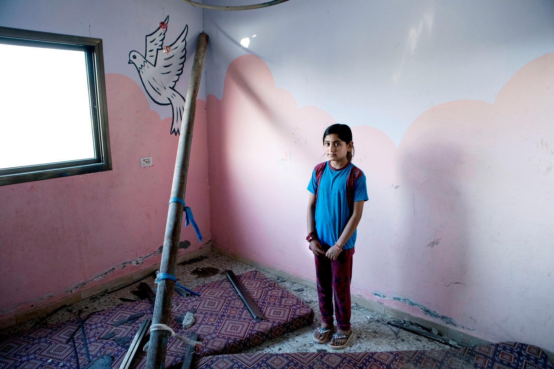 I det rosa rummet med fåglar på väggarna bodde Rafah. Här står hon i ruinerna av det som var hennes och systerns älskade krypin.