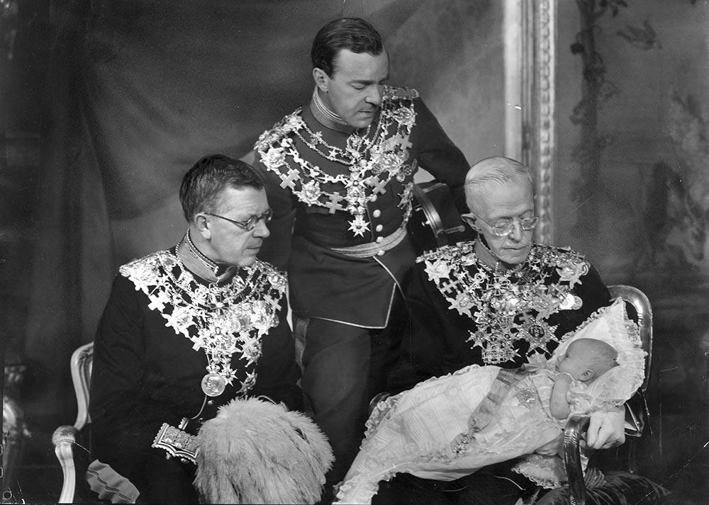 Prins Carl Gustaf tillsammans i sin farfars fars famn, Gustaf V. Bredvid sitter prinsens farfar blivande Gustaf VI och ståendes syns prinsens pappa prins Gustaf Adolf.