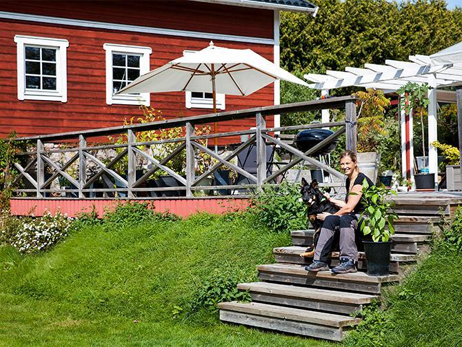 Gabriella och hunden Kolbjörn på trappan till det 100 kvadratmeter stora trädäcket.