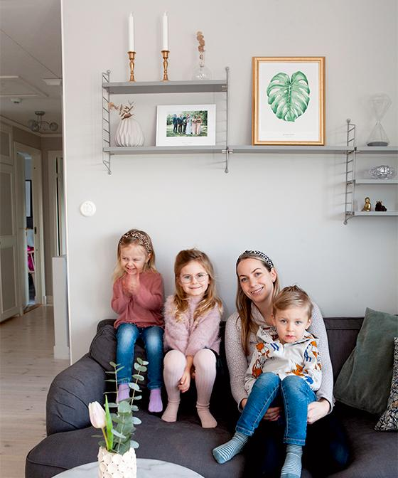 Mys i vardagsrummet. Hanna med sina barn Elsa, Thilde och Charlie i knät. Soffa från Ikea och stringhyllor på väggen.