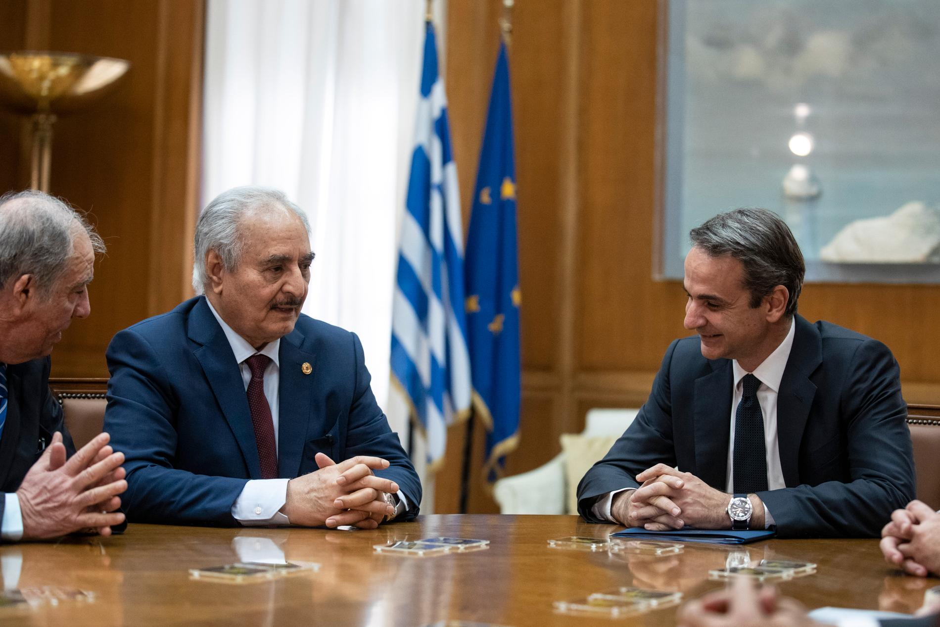 Krigsherren Khalifa Haftar, näst längst till vänster, uppvaktas av många världsledare som hoppas att han ska gå med på att lägga ned vapnen i Libyen. Bild från möte med Greklands premiärminister Kyriakos Mitsotakis, till höger, på fredagen.