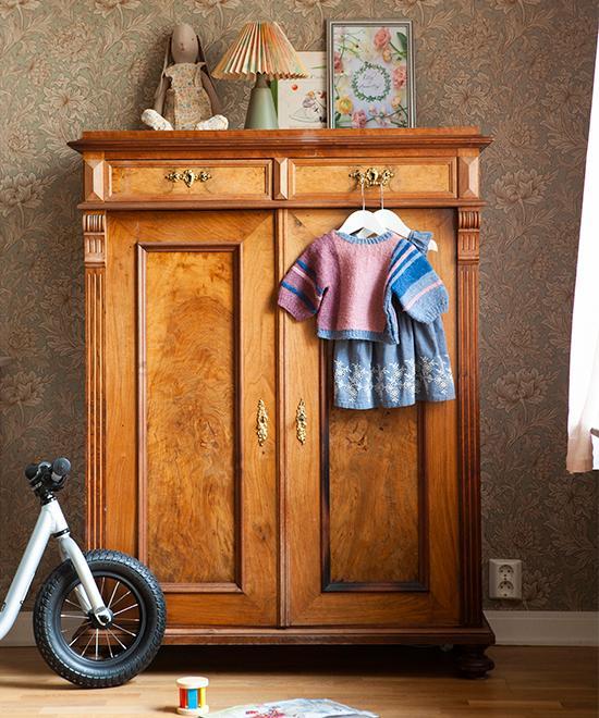 Blomstrande väggar i Ellys rum. Tapet av William Morris i mönster Chrysanthe - mum toile. Skåpet är arvegods efter Hannas morföräldrar. Lampan på skåpet är köpt på loppis. Den stickade tröjan har Hannas mamma stickat och klänningen är köpt på Blocket.