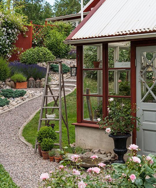 Tomten är kuperad och uppbyggd i olika nivåer, och från boningshuset slingrar sig en grusbelagd gång ner till växthuset.