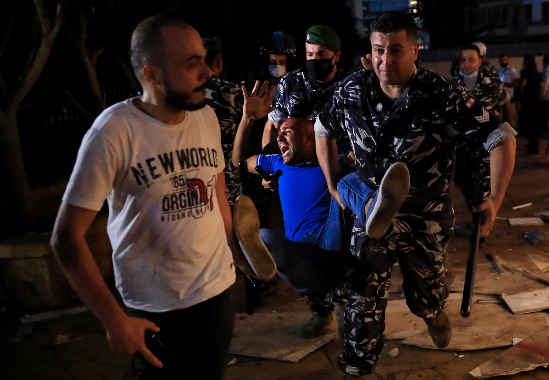 Polismän bär iväg en man som skadats i protester i Libanons huvudstad Beirut. Protesterna gäller vad som uppfattas som myndigheternas försök att förhindra en utredning av vad som låg bakom den omfattande explosionen. Arkivbild.