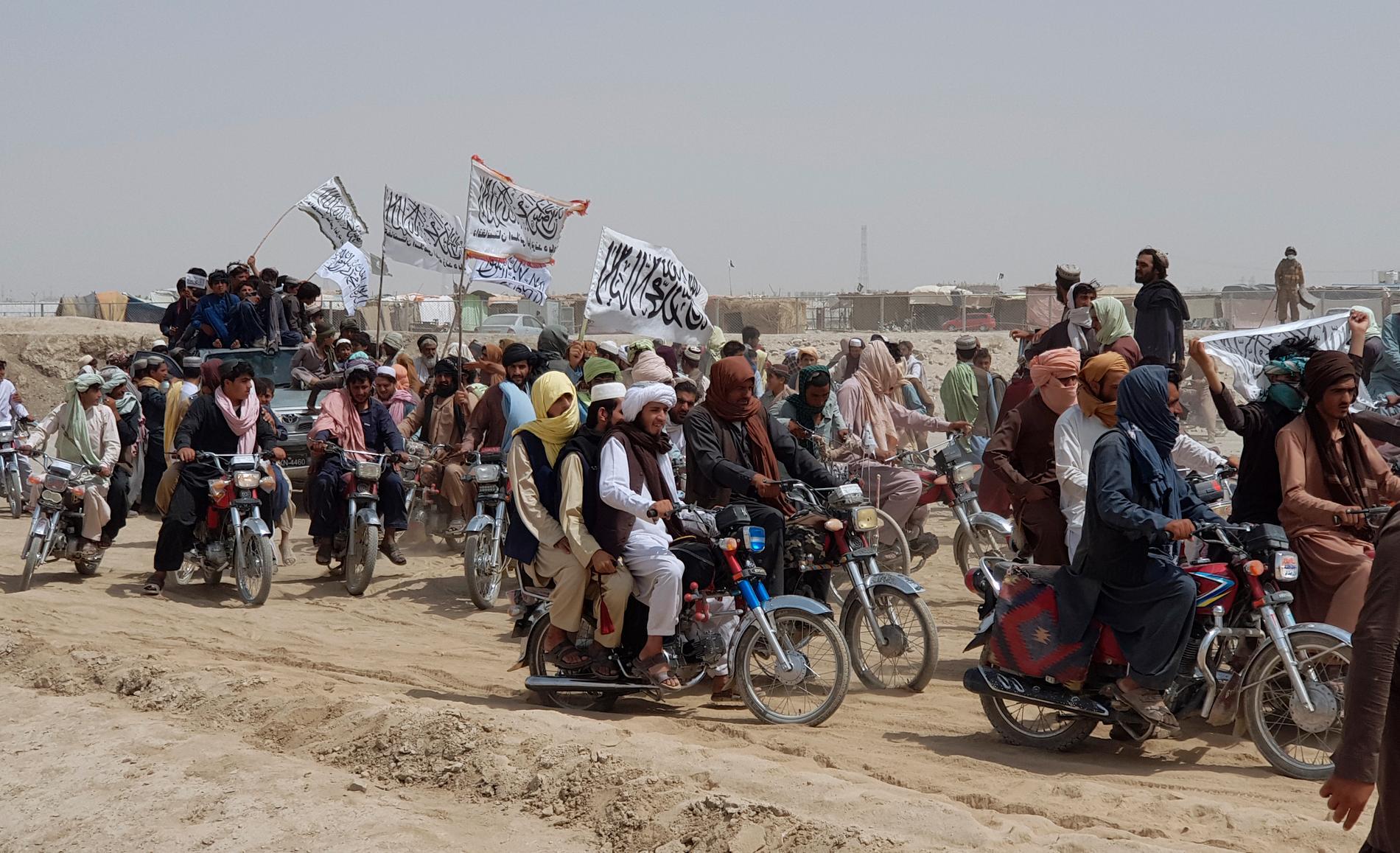 Talibananhängare bär rörelsens vita flagga vid gränsområdet mellan Afghanistan och Pakistan den 14 juli i år. Talibanerna, som uppskattas ha ett stöd på cirka 15 procent bland den afghanska befolkningen, har under juli intagit flera viktiga gränsövergångar i de upptrappade striderna.